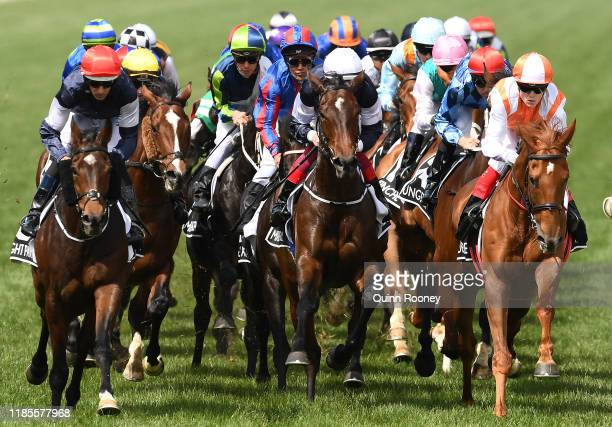Hugh Bowman riding Twilight Payment and Craig Williams riding Vow and Declare leads the field around the first bend in the Lexus Melbourne Cup during...