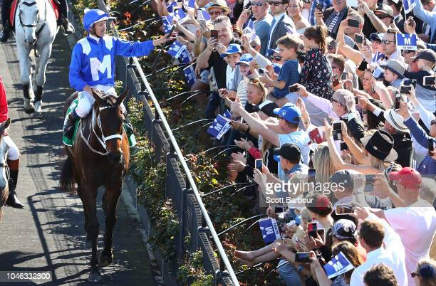 Hugh Bowman riding Winx celebrates as he returns to the mounting yard after winning race 5 the TAB Turnbull Stakes during Melbourne Racing at...