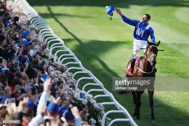 Hugh Bowman throws his helmet into the crowd on returning to scale after winning on Winx to win race 9 the Ladbrokes Cox Plate during Cox Plate Day...