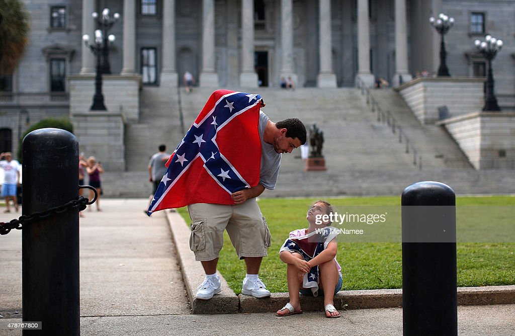 Hugh Crawford of Lexington, South Carolina speaks with his daughter Holli Crawford, age 7, as they join a group of demonstrators on the grounds of the South Carolina State House calling for the Confederate flag to remain on the State House grounds June 27, 2015 in Columbia, South Carolina. Earlier in the week South Carolina Gov. Nikki Haley expressed support for removing the Confederate flag from the State House grounds in the wake of the nine murders at Mother Emanuel A.M.E. Church in Charleston, South Carolina.