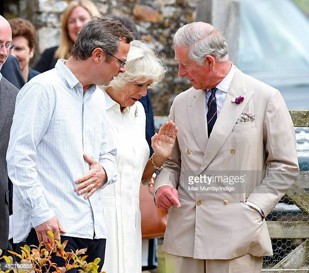 Hugh FearnleyWhittingstall looks on as Camilla Duchess of Cornwall swats away an insect on Prince Charles Prince of Wales's suit jacket as they tour...