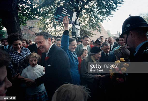 Hugh Gaitskell 1958 during labour party political campaign arriving in Rugby UK wife on rt being presented with a bunch of yellow roses He later...