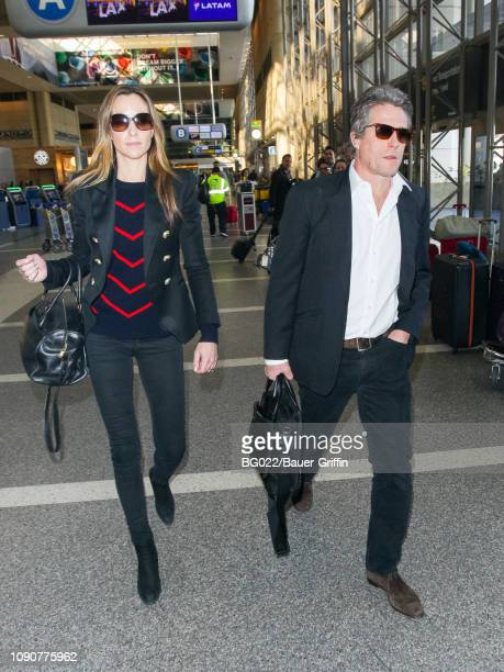 Hugh Grant and Anna Eberstein are seen at Los Angeles International Airpor on January 28 2019 in Los Angeles California