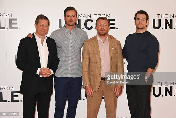 Hugh Grant Armie Hammer director Guy Ritchie and Henry Cavill attend a photocall for The Man From UNCLE at Claridge's Hotel on July 23 2015 in London...