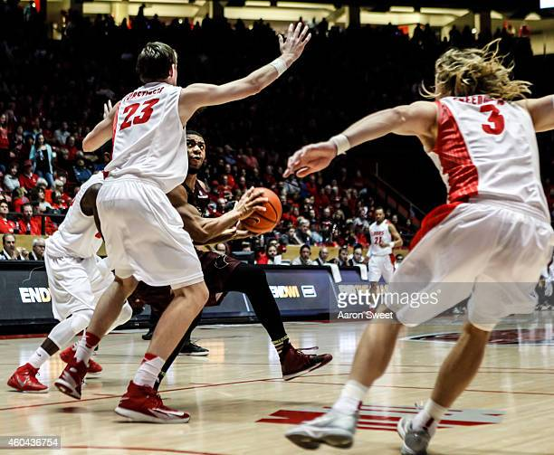 Hugh Greenwood and teammate Joe Furstinger of the New Mexico Lobos defend against Justin Roberson of the LouisianaMonroe Warhawks as he looks for an...
