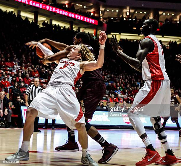 Hugh Greenwood and teammate Obij Aget of the New Mexico Lobos fight for a rebound against Marvin Williams of the LouisianaMonroe Warhawks during...
