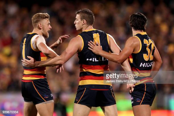 Hugh Greenwood Josh Jenkins and Darcy Fogarty of the Crows celebrate a goal during the 2018 AFL round 02 match between the Adelaide Crows and the...