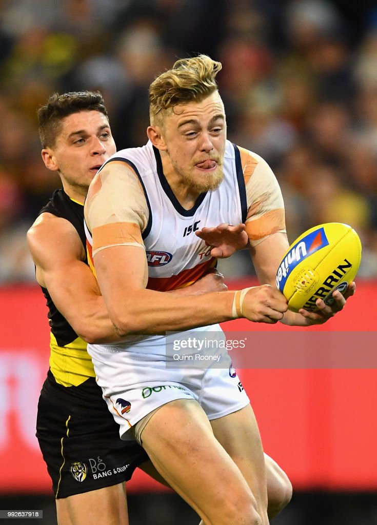Hugh Greenwood of the Crows handballs whilst being tackled by Dion Prestia of the Tigers during the round 16 AFL match between the Richmond Tigers and the Adelaide Crows at Melbourne Cricket Ground on July 6, 2018 in Melbourne, Australia.