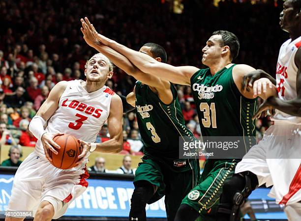 Hugh Greenwood of the New Mexico Lobos drives to the basket against Gian Clavell and JJ Avila of the Colorado State Rams during their game at The...
