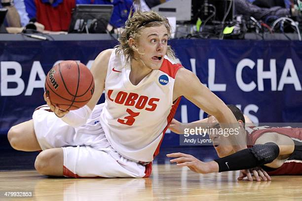 Hugh Greenwood of the New Mexico Lobos slides to grab a loose ball against Dwight Powell of the Stanford Cardinal in the second half during the...