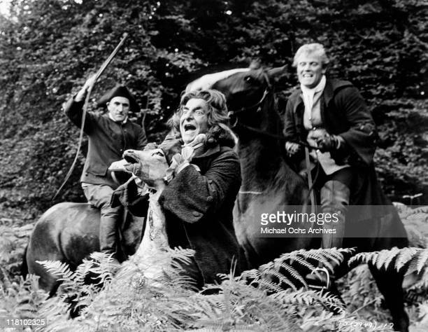 Hugh Griffiths hold up the head of a dead deer in a scene from the film 'Tom Jones' 1963