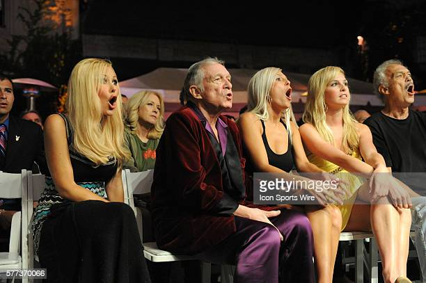 Hugh Hefner and his girlfriends react to a big hit during the Strikeforce at the Mansion 2 mixed martial arts event at the Playboy Mansion in Beverly...