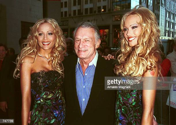 Hugh Hefner center celebrates the upcoming May issue of Playboy with his girlfriends cover girls Sandy and Mandy Bentley April 12 2000 in New York...