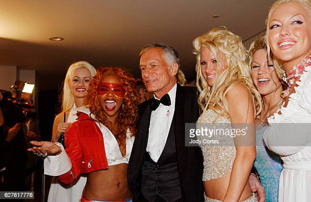Hugh Hefner Lil' Kim and his Hefner's girlfriends greet each other at the Warner Music Group and Entertainment Weekly postGrammy party