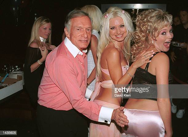Hugh Hefner spanks playboy models Izabella Kasprzyk and Bridget Marquardt during their birthday dinner party at Joya restaurant on September 25, 2002...