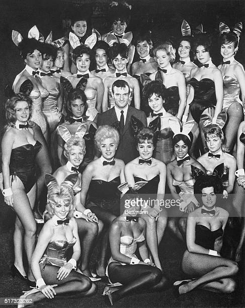 Hugh Hefner with many of the costumed waitresses from his Playboy Clubs known due to the outfits as 'bunnies'