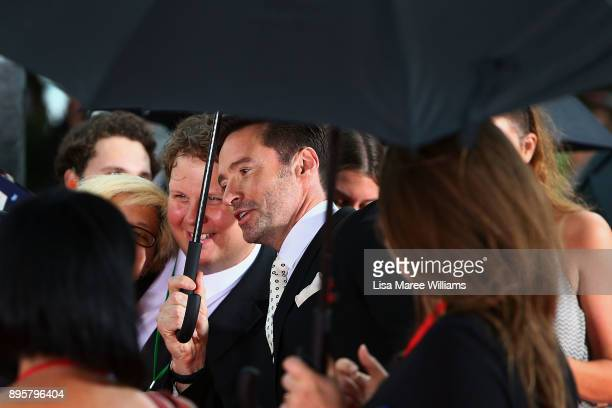 Hugh Jackman greets fans in the rain during the Australian premiere of The Greatest Showman at The Star on December 20 2017 in Sydney Australia