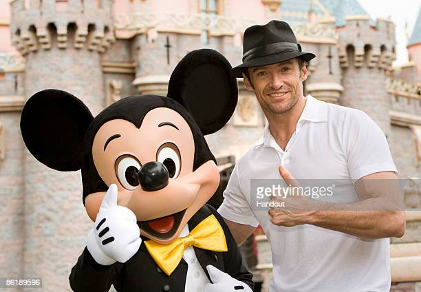 Hugh Jackman poses with Mickey Mouse outside Sleeping Beauty Castle at Disneyland in Anaheim Calif On Thursday