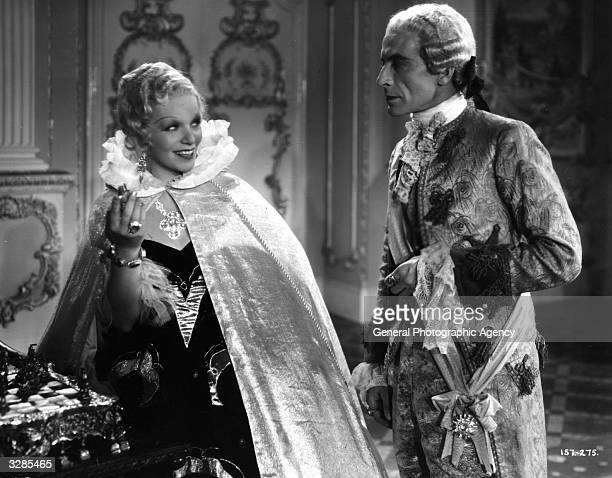 Hugh Miller and Gitta Alpar in a teasing scene from the film 'I Give My Heart' adapted from the operetta success 'The Dubarry' and directed by Marcel...