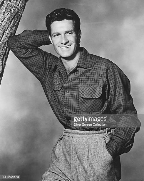 Hugh O'Brian US actor wearing grey trousers and a dark fine check shirt leaning with his right elbow against a tree trunk his left hand in the pocket...