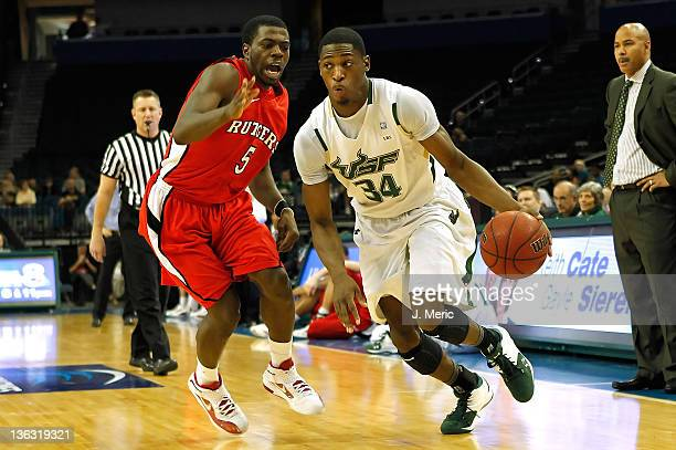 Hugh Robertson of the South Florida Bulls drives past Eli Carter of the Rutgers Scarlet Knights during the game at the Tampa Bay Times Forum on...