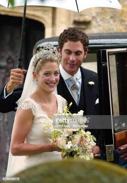 Hugh Van Cutsem holds an umberella for his new bride Rose Astor after their wedding