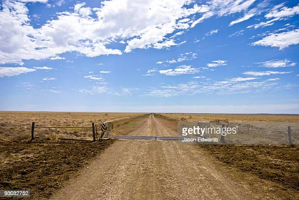 A rough dirt track and cattle grid forms a major road in the Outback.