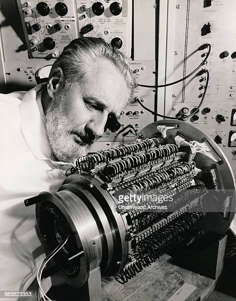 A Hughes Aircraft Company engineer examines the 294 'readwrite heads' that protrude from the outer cylinder of the Mark II Mod 7 series 15 million...