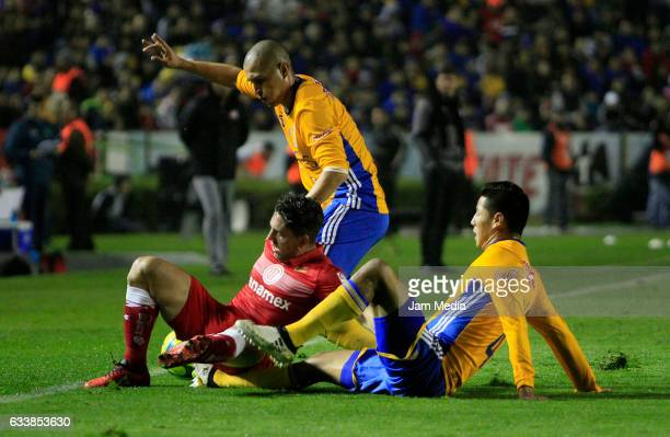 Hugo Ayala Jorge Torres of Tigres UANL and Gabriel Hauche of Toluca fight for the ball during the 5th round match between Tigres and Toluca as part...