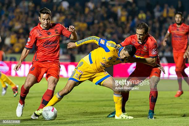 Hugo Ayala of Tigres fights for the ball with Juan Rodriguez and Emanuel Loeschbor of Morelia during the 2nd round match between Tigres UANL and...