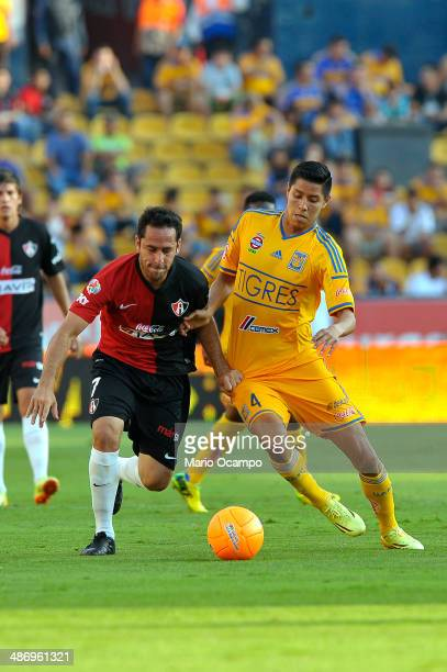 Hugo Ayala of Tigres fights for the ball with Oscar Razo of Atlas during a match between Tigres UANL and Atlas as part of 17th round Clausura 2014...