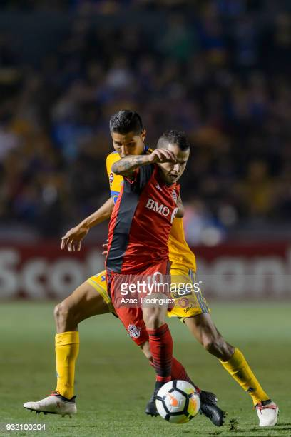 Hugo Ayala of Tigres fights for the ball with Sebastian Giovinco of Toronto during the quarterfinals second leg match between Tigres UANL and Toronto...