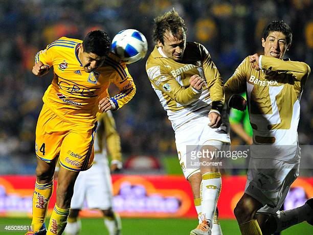 Hugo Ayala of Tigres heads the ball as Martin Romagnoli and Marco Palacios try to stop him during a match between Tigres UANL and Pumas UNAM as part...