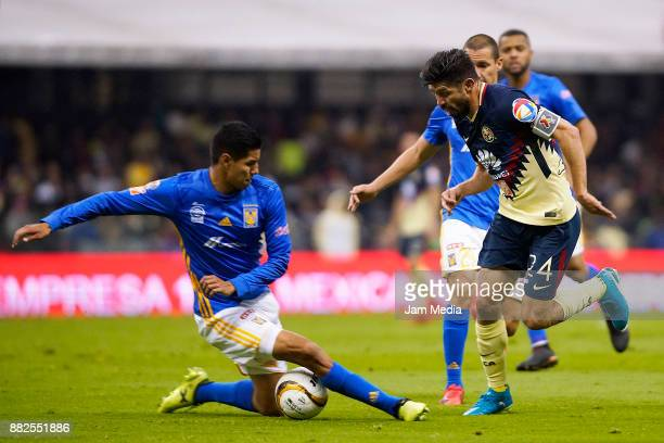 Hugo Ayala of Tigres slides to defend against Oribe Peralta of America during the semifinal first leg match between America and Tigres UANL as part...