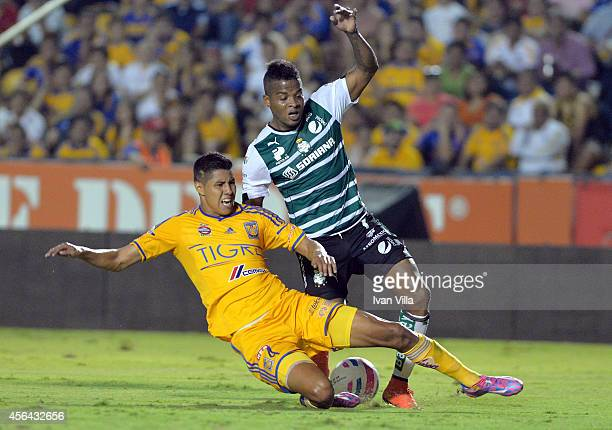 Hugo Ayala of Tigres slides to steal the ball from Andres Renteria of Santos during a match between Tigres UANL v Santos Laguna as part of 11th round...