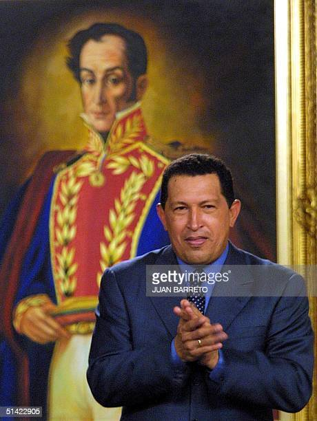 Hugo Chavez, president of Venezuela, stands in front of a painting of Simon Bolivar, as he applauds during a meeting in the Presidential Palace in...
