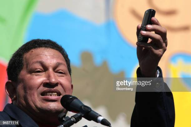 Hugo Chavez Venezuela's president waves his mobil phone after receiving a call from Cuban leader Fidel Castro during the Meeting for the Friendship...