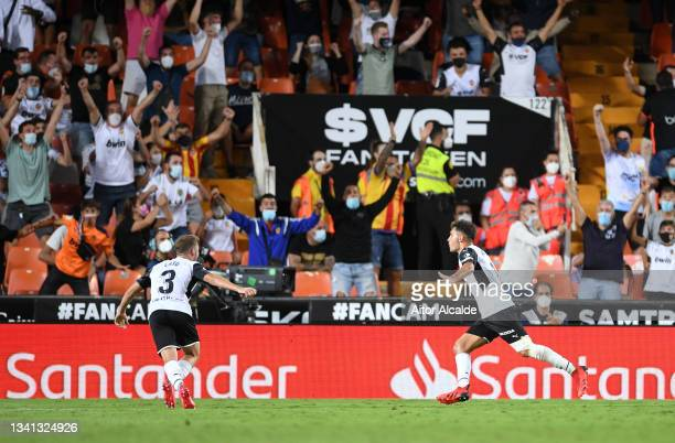 Hugo Duro of Valencia celebrates with teammate Toni Lato after scoring their side's first goal during the La Liga Santander match between Valencia CF...
