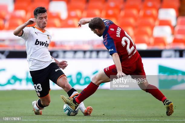 Hugo Guillamon of Valencia CF challenges for the ball against Darko Brasanac of CA Osasuna during the Liga match between Valencia CF and CA Osasuna...