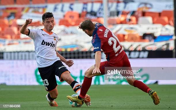 Hugo Guillamon of Valencia competes for the ball with Darko Brasanac of Osasuna during the Liga match between Valencia CF and CA Osasuna at Estadio...