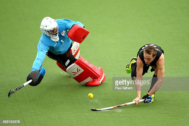 Hugo Inglis of New Zealand shoots past George Pinner of England to score in the shoot out in the bronze medal match between New Zealand and England...