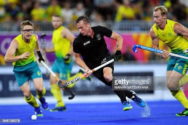 TOPSHOT Hugo Inglis of New Zealand vies for the ball with Australia's Matthew Dawson and Aran Zalewski during their men's field hockey gold medal...
