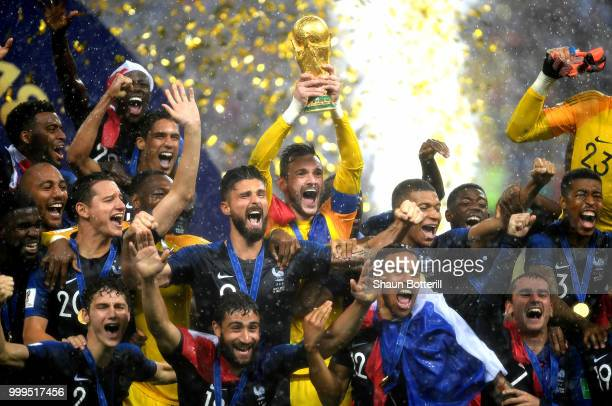 TOPSHOT France's goalkeeper Hugo Lloris kisses the trophy with his daughters as they celebrate during the trophy ceremony after winning the Russia...