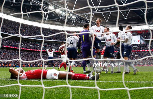 Hugo Lloris of Tottenham Hotspur celebrates with Harry Kane and teammates after saving a penalty whilst PierreEmerick Aubameyang of Arsenal looks...