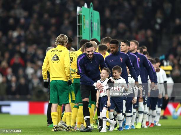 Hugo Lloris of Tottenham Hotspur embraces a Tottenham Hotspur mascot after shaking hands with the Norwich City players prior to the Premier League...