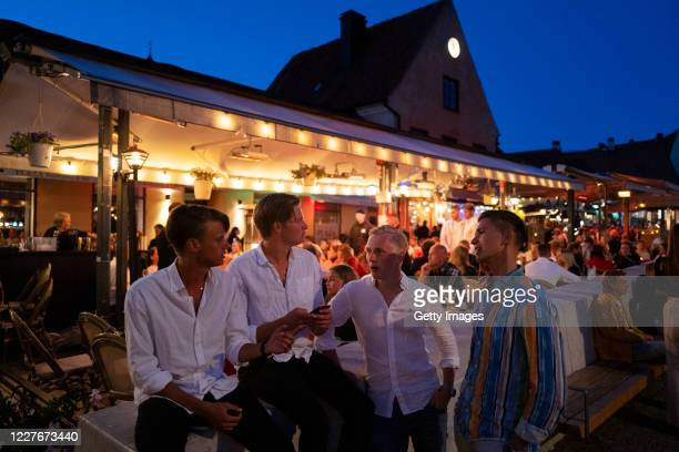 Hugo Reimer, William Florin, Edvin Johansson and Jeremia Magnusson chat outside a restaurant on July 17, 2020 in Gotland, Sweden. Sweden largely...