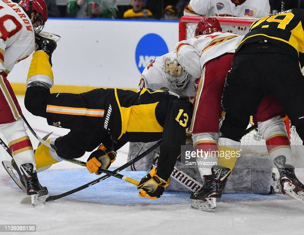 Hugo Reinhardt of the American International Yellow Jackets drives in front of the net as Filip Larsson of the Denver Pioneers stops a Yellow...