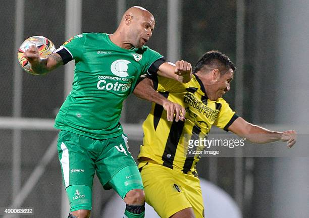 Hugo Soto player of La Equidad fights for the ball with Martin Arzuaga player of Alianza Petrolera during a 14th round match between La Equidad and...