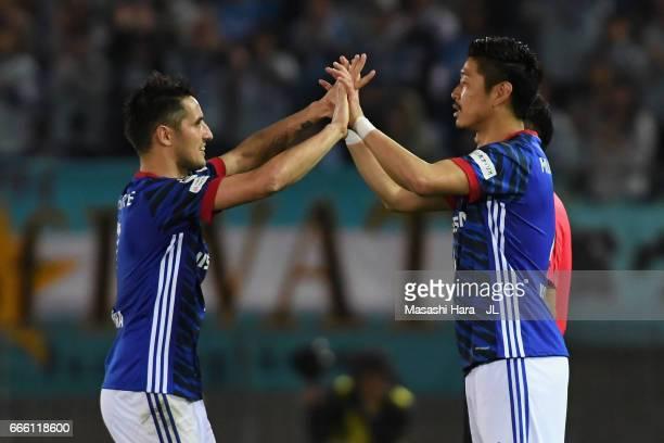 Hugo Vieira of Yokohama F.Marinos high fives with Yuzo Kurihara as he is substituted during the J.League J1 match between Yokohama F.Marinos and...