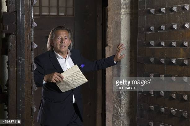 Hugues de Sade a descendant of French writer the Marquis de Sade poses with a letter of the Marquis de Sade in the Vincennes castle on July 2 2014 in...